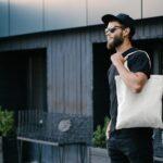 Młody mężczyzna trzymający białą tekstylną torbę ekologiczną